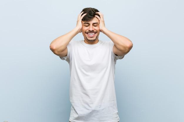 Der junge kaukasische mann, der ein weißes t-shirt trägt, lacht freudig, hände auf kopf halten. glück-konzept.