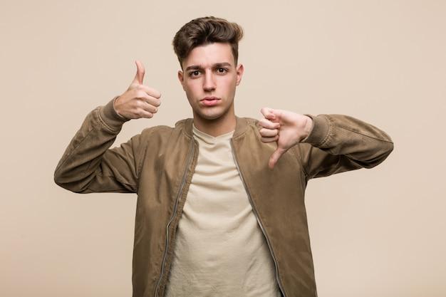 Der junge kaukasische mann, der eine braune jacke zeigt daumen hoch und daumen unten trägt, wählen schwierig