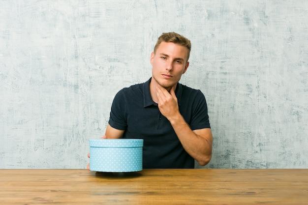 Der junge kaukasische mann, der eine geschenkbox auf einem tisch hält, leidet die schmerz in der kehle wegen eines virus oder einer infektion.