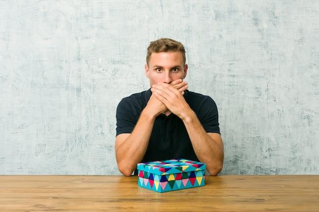 Der junge kaukasische mann, der eine geschenkbox auf einer tabelle hält, entsetzte bedeckungsmund mit den händen.