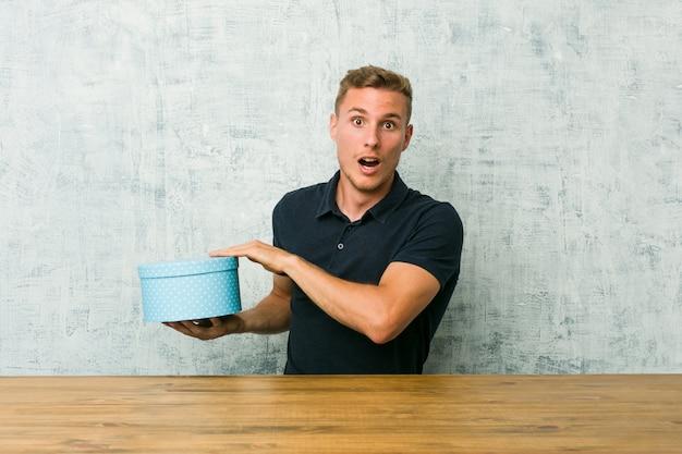 Der junge kaukasische mann, der eine geschenkbox auf einer tabelle hält, entsetzte und überraschte das halten eines kopienraumes zwischen händen.