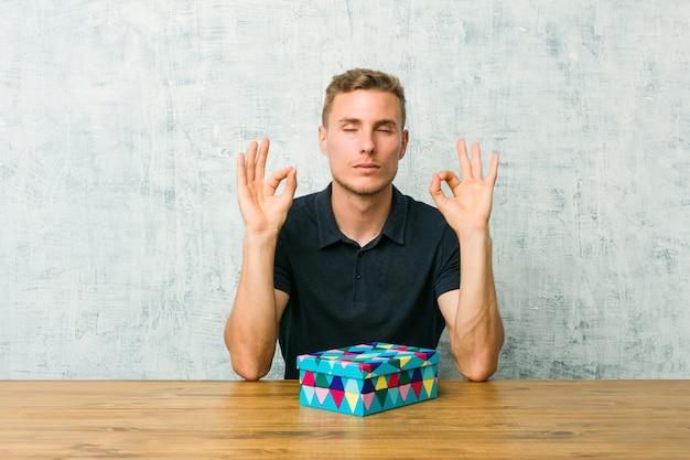 Der junge kaukasische mann, der eine geschenkbox auf einer tabelle hält, entspannt sich nach hartem arbeitstag, sie führt yoga durch.