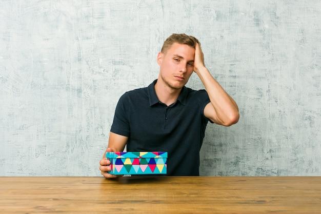 Der junge kaukasische mann, der eine geschenkbox auf einer tabelle hält, ermüdete und sehr schläfrig, hand auf kopf halten.