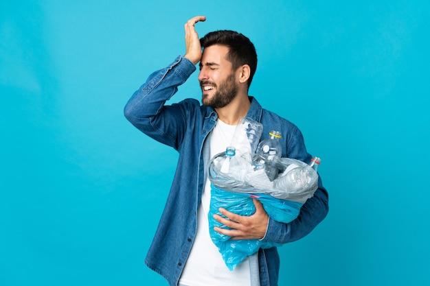 Der junge kaukasische mann, der eine tasche voller plastikflaschen hält, um isoliert auf blau zu recyceln, hat etwas realisiert und beabsichtigt die lösung