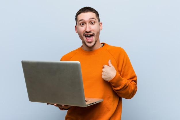 Der junge kaukasische mann, der einen laptop anhält, überraschte das zeigen auf und breit lächelte.