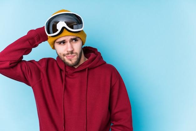 Der junge kaukasische mann, der einen ski trägt, kleidet die getrennte berührung zurück vom kopf, denkt und trifft eine wahl.