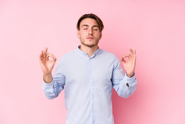 Der junge kaukasische mann, der in einer rosa lokalisierten wand aufwirft, entspannt sich nach hartem arbeitstag, sie führt yoga durch.