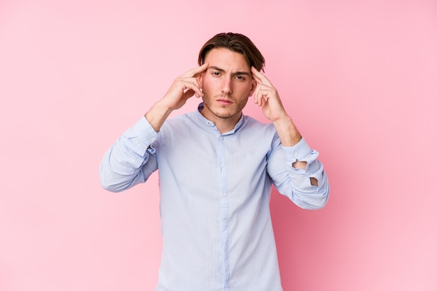 Der junge kaukasische mann, der in einer rosa wand lokalisiert aufwirft, konzentrierte sich auf eine aufgabe und hielt die zeigefinger, die kopf zeigen.