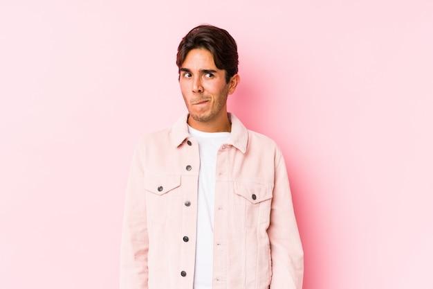 Der junge kaukasische mann, der in einer rosa wand lokalisiert verwirrt aufwirft, fühlt sich zweifelhaft und unsicher.