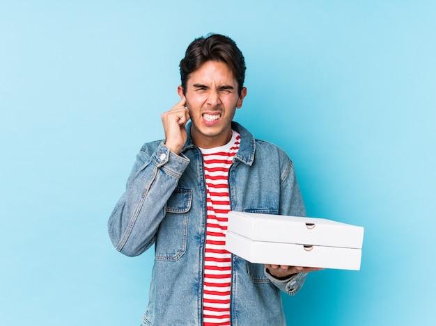 Der junge kaukasische mann, der pizzas hält, lokalisierte bedeckungsohren mit den händen.