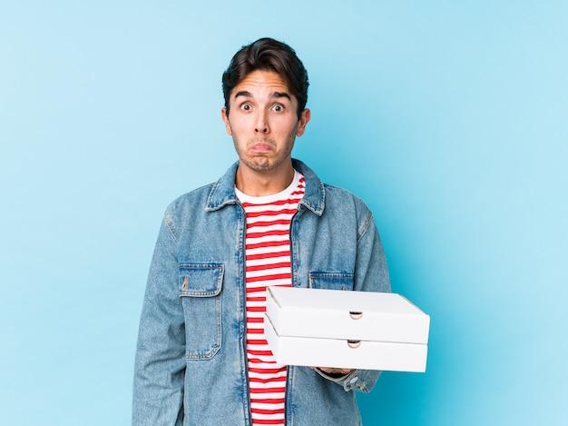 Der junge kaukasische mann, der pizzas hält, lokalisierte die schultern mit den schultern und die offenen augen, die verwirrt wurden.