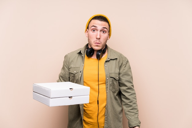 Der junge kaukasische mann, der pizzas hält, zuckt die schultern und die offenen augen, die verwirrt werden.