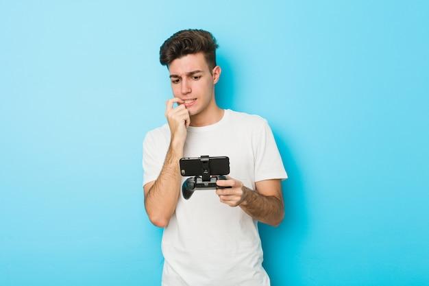 Der junge kaukasische mann, der videospiele mit telefon spielt, entspannte sich das denken an etwas, das einen kopienraum betrachtet.
