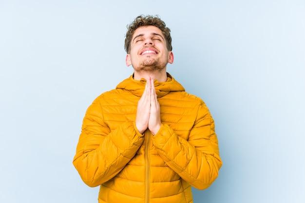 Der junge kaukasische mann des blonden lockigen haares, der händchen haltend im gebet nahe mund hält, fühlt sich zuversichtlich.