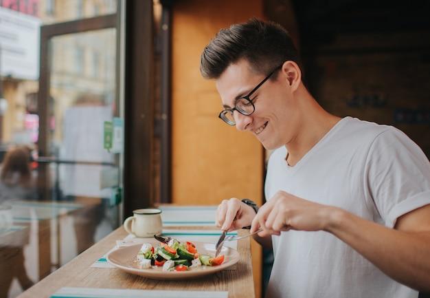 Der junge kaukasische mann mit gläsern, die einen gesunden salat essen.