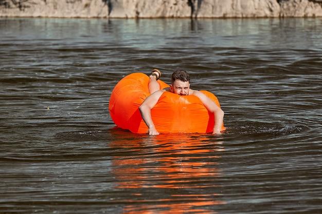 Der junge kaukasische mann schwimmt während seines urlaubs auf dem orangefarbenen luftsofa auf dem fluss mit felsen im hintergrund.