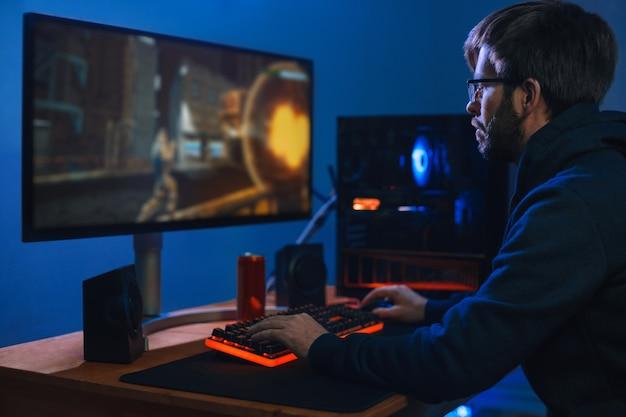 Der junge kaukasische profispieler spielt im online-cybersportspiel zu hause in seinem zimmer auf einem modernen pc.