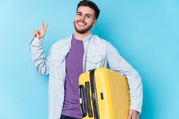 Der junge kaukasische reisendmann, der einen koffer hält, lokalisierte das frohe und sorglose zeigen eines friedenssymbols mit den fingern.