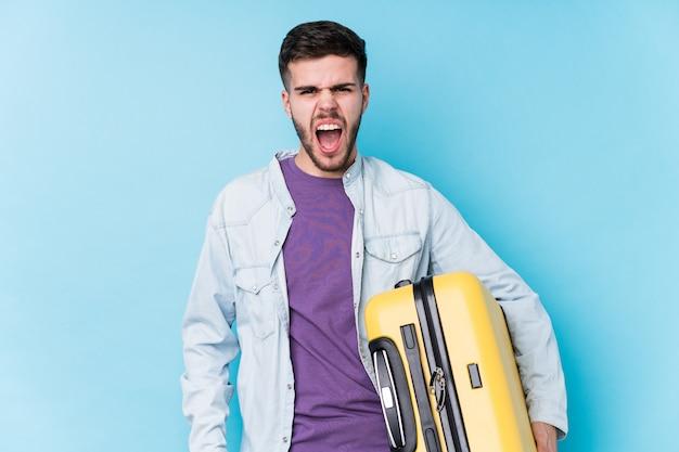 Der junge kaukasische reisendmann, der einen koffer hält, lokalisierte das schreien sehr verärgert und aggressiv.