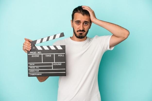 Der junge kaukasische schauspielermann, der clapperboard isoliert auf blauem hintergrund hält, ist schockiert, sie hat sich an ein wichtiges treffen erinnert.