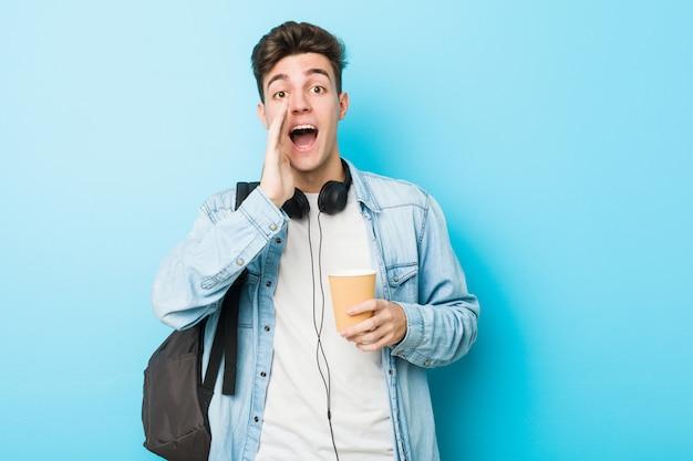 Der junge kaukasische studentenmann, der ein hält, nehmen das kaffeeschreien weg, das zur front aufgeregt ist.