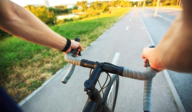 Der junge kerl fährt mit dem fahrrad durch die stadt