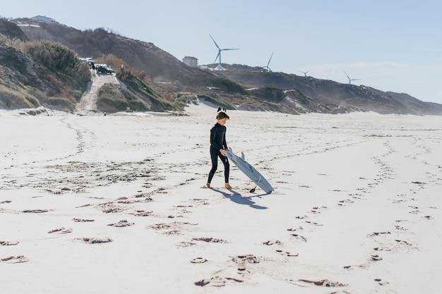 Der junge knetet vor dem surfen am strand und rennt mit einem surfbrett ins wasser