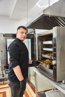 Der junge koch in einer schwarzen tunika bereitet catering-snacks zu
