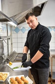 Der junge koch in schwarzer tunika bereitet catering-snacks zu