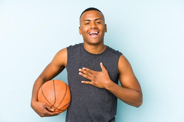 Der junge kolumbianische mann, der isoliert basketball spielt, lacht laut und hält die hand auf der brust.