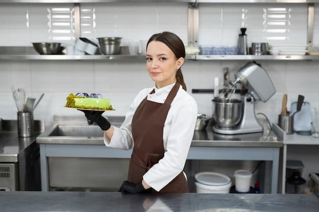 Der junge lächelnde brünette koch hält einen mousse-kuchen, der mit handgemachten pralinen verziert ist.