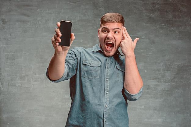 Der junge lächelnde kaukasische geschäftsmann auf grau mit telefon
