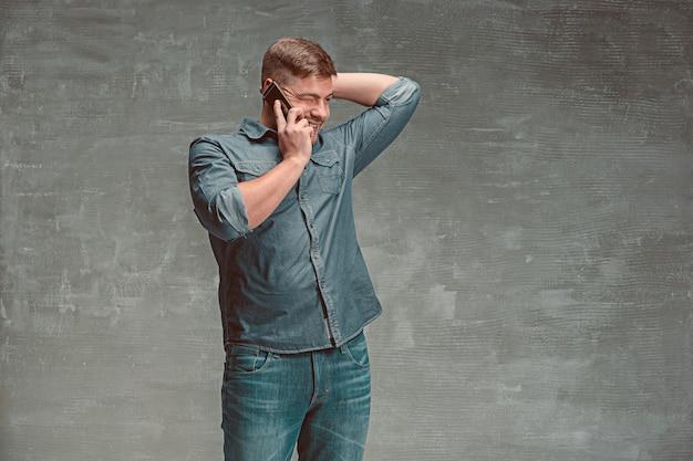 Der junge lächelnde kaukasische geschäftsmann auf grauem studio, der auf handy spricht
