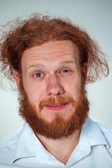 Der junge lächelnde mann mit den langen roten haaren, die kamera betrachten