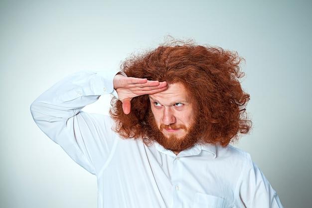 Der junge lächelnde mann mit den langen roten haaren schaut spielerisch weg