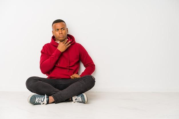 Der junge lateinamerikanische mann, der isoliert auf dem boden sitzt, leidet unter halsschmerzen aufgrund eines virus oder einer infektion.
