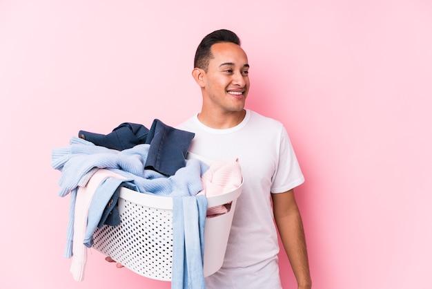 Der junge lateinamerikanische mann, der vereinzelt schmutzige kleidung aufhebt, schaut lächelnd, fröhlich und angenehm beiseite.