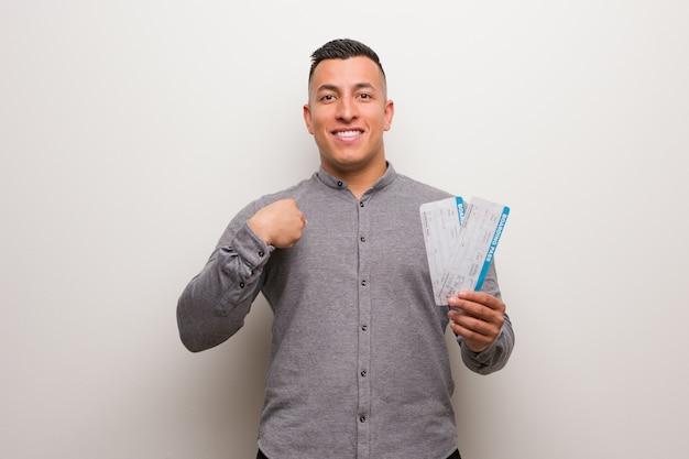 Der junge lateinische mann, der die flugtickets überrascht hält, fühlt sich erfolgreich und wohlhabend