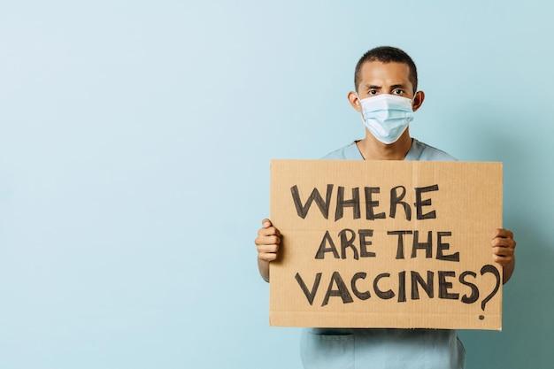 Der junge latinx-gesundheitspersonal hält ein banner, auf dem die impfstoffe stehen?