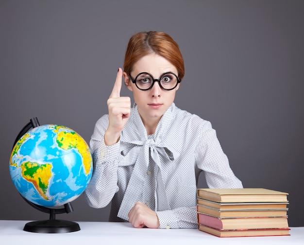 Der junge lehrer in gläsern mit büchern und globus.