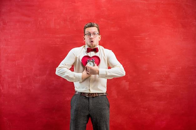 Der junge lustige mann mit abstraktem herzen und uhr auf rotem studio. konzept - zeit zu gratulieren