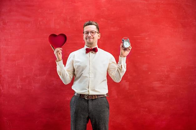 Der junge lustige mann mit abstraktem herzen und uhr auf rotem studiohintergrund. konzept - zeit zu gratulieren