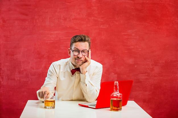 Der junge lustige mann mit cognac, der mit laptop am valentinstag auf rotem hintergrund sitzt. konzept - unglückliche liebe
