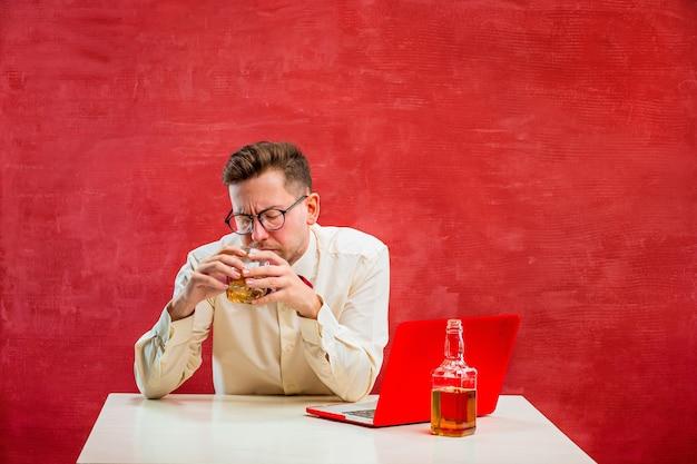 Der junge lustige mann mit cognac, der mit laptop am valentinstag auf rotem studio sitzt.