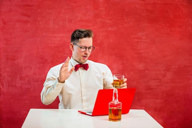 Der junge lustige mann mit cognac, der mit laptop am valentinstag auf rotem studiohintergrund sitzt. konzept - unglückliche liebe