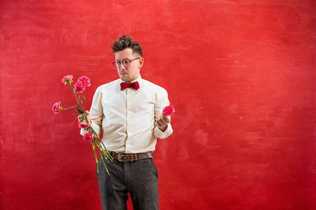 Der junge lustige mann mit gebrochenem blumenstrauß auf rotem studiohintergrund. konzept - unglückliche liebe