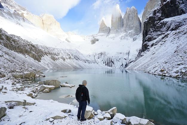 Der junge männliche asiatische soloreisende, der an der basis von torres del paine, patagonia herein steht