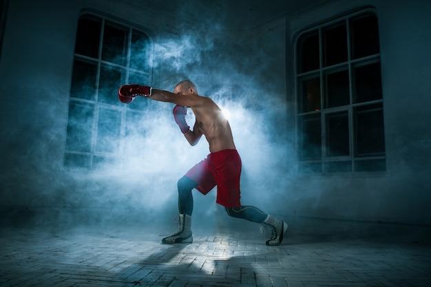 Der junge männliche athlet kickboxen auf einem blauen rauch
