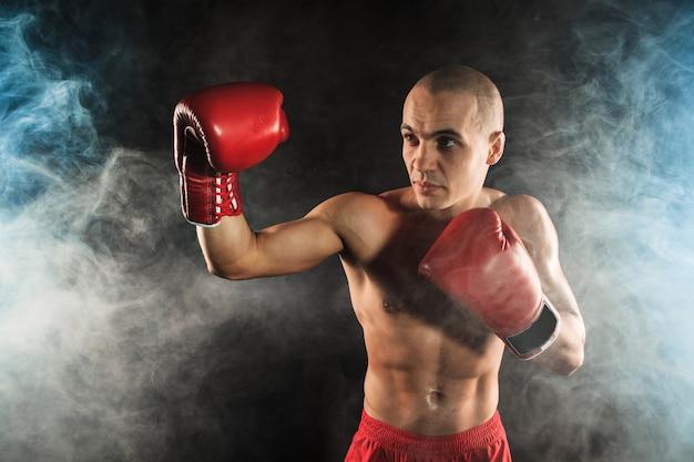 Der junge männliche athlet kickboxen auf einem hintergrund des blauen rauches