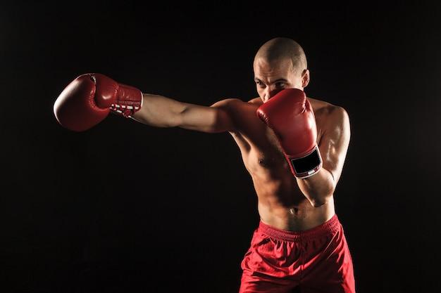 Der junge männliche athlet kickboxen auf einem schwarzen hintergrund